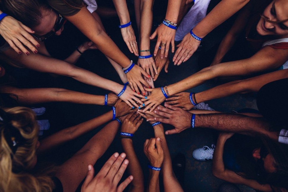 A circle of hands of people working together on a charity project.