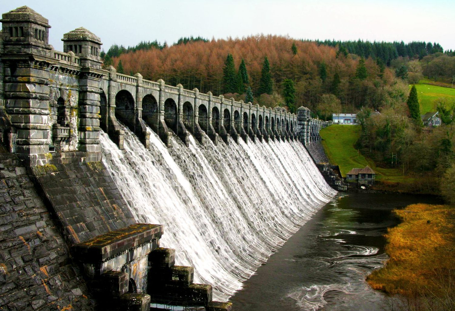 Evocative image: multiple trickles of water, regimented, carefully controlled, emerging from a dam.