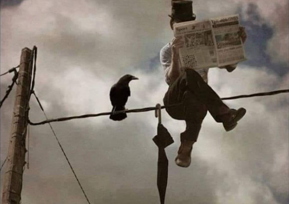 Businessman seated on a telephone wire. Watched by a crow.