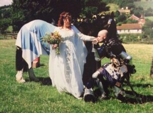 Kneeling groom, gorgeous bride, dressed horse, idyllic setting.