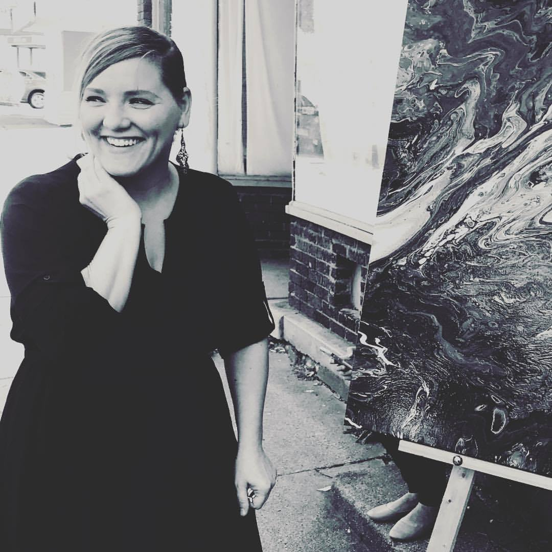 Black and white photo of a blond woman in a black dress stands smiling in front of her artwork.