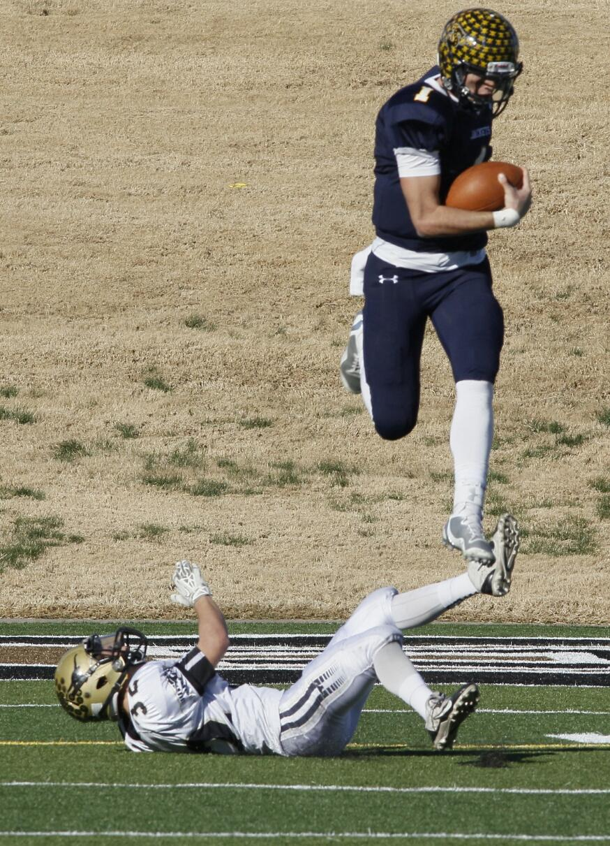 Jarrett Stidham leaps a Big Spring defender in a Region I-4A Division I semifinal at Shotwell Stadium in Abilene on November 28. || Photo by RUSSELL HUFFMAN