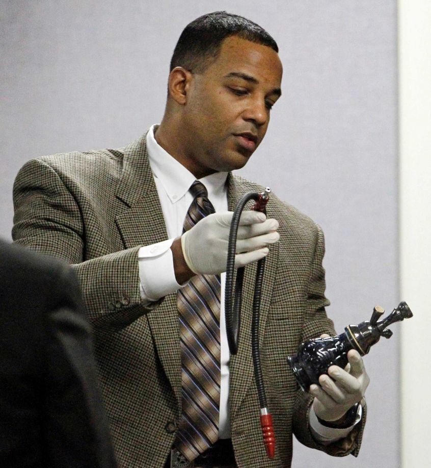 Texas Ranger David Armstrong holds a hookah, part of evidence seized at defendant Eddie Ray Routh's house, during Routh's capital murder trial at the Erath County, Donald R. Jones Justice Center in Stephenville, Texas, Friday, Feb. 13, 2015. Former Marine Cpl. Routh, 27, of Lancaster, is charged with the 2013 deaths of former Navy SEAL Chris Kyle and his friend Chad Littlefield at a shooting range near Glen Rose, Texas. (AP Photo/The Fort Worth Star-Telegram, Paul Moseley, Pool)