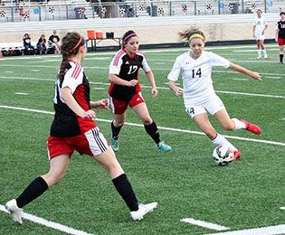 Bayleigh Chaviers dribbles between two Mineral Wells defenders during a 4-0 Stephenville win Tuesday at Bearcat Stadium in Aledo. || BRAD KEITH/TheFlashToday.com