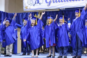 """Kinder grads on stage singing """"I'm a Huckabay kid, I don't want to grow up."""""""