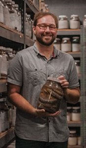 Dr. Jesse Meik holds a jar of preserved specimens of the rattlesnake he is researching. (Photo by Cameron Cook)