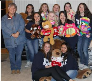 The 6-4A district champion freshman Honeybees with teddy bears for donation through 2nd Monday GIVE BACK, a project of EXIT Realty Holland & Associates, represented in the photo by agent Trudy Spears. || Contributed