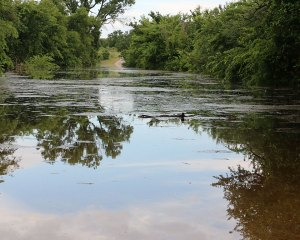 County Road 520 is impassable with a soil conservation lake filled to capacity blocking the roadway.