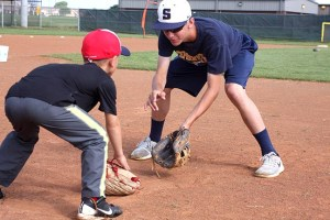 Derek Gifford shows a youngster proper field position during Yellow Jacket Baseball Camp Monday morning. Gifford, 15, will compete with CBA Texas in the USA Baseball Championship for 17U teams later this month in Florida. || TheFlashToday.com photo by BRAD KEITH