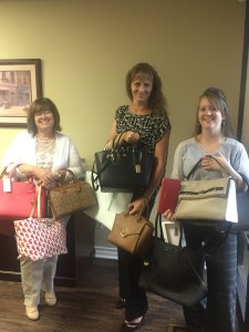 Paluxy River Children's Advocacy Center staffers show off designer handbags that will be up for grabs at an August 25 fundraiser.
