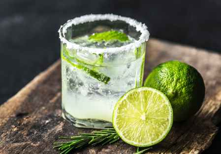 sliced lime fruit near clear drinking glass with lime juice on brown wooden plank
