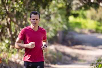 man running on path surrounded with trees