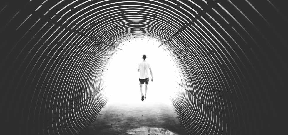 grayscale photo of man walking in hole