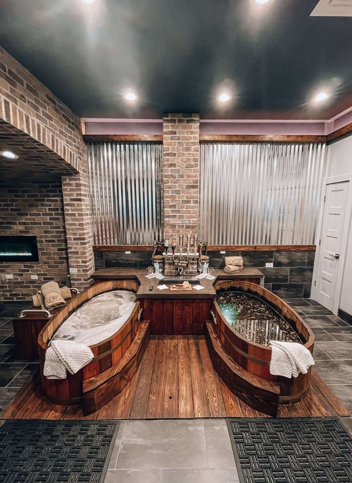 Two hot tubs inside the Beer Spa room next to beer taps
