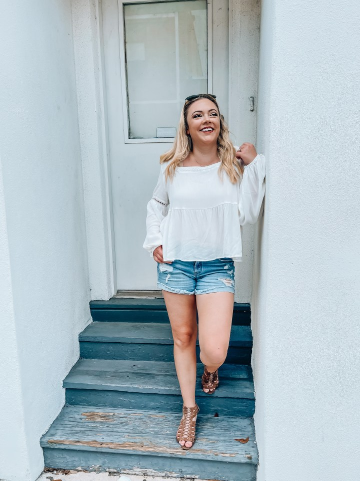 Florida Hop Mama walking around smiling in Winter Park, Florida in a white shirt and denim shorts