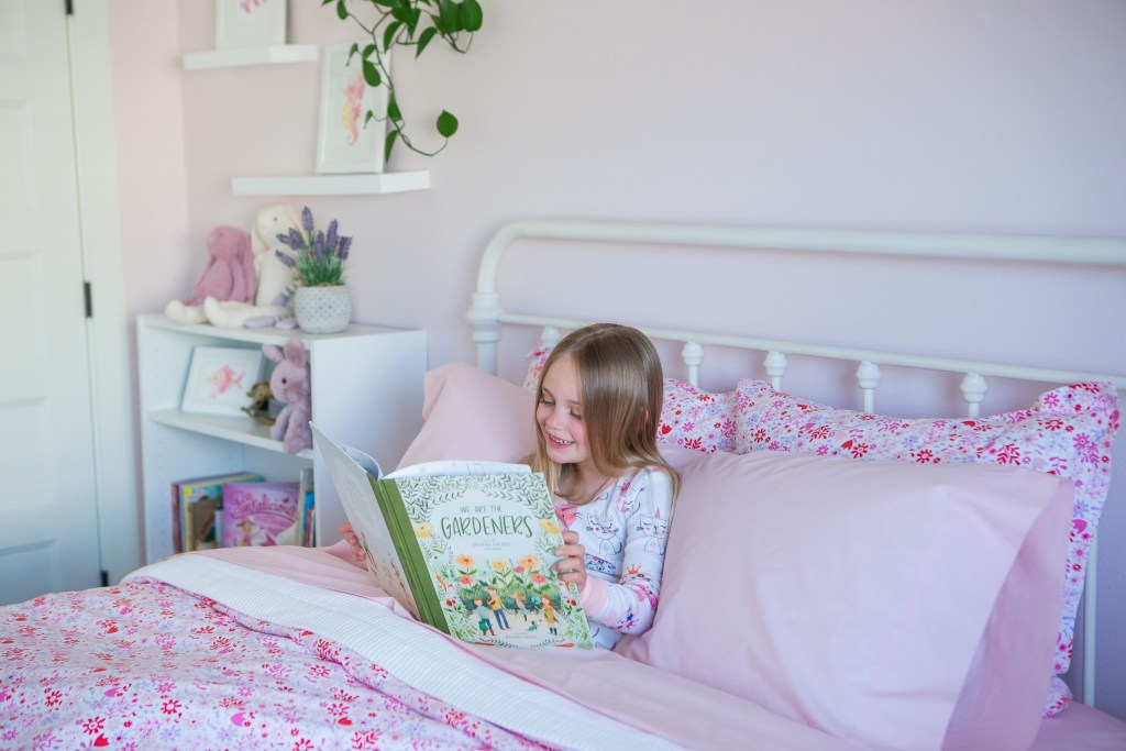 Little girl reading book in pink floral bedroom