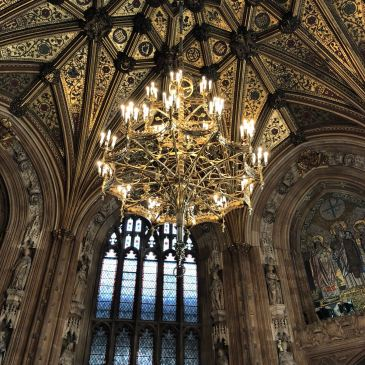 Beautiful chandelier hanging off the ornate ceiling of the houses of parliament