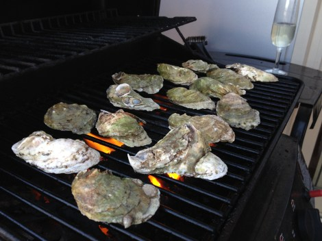Oysters on the BBQ with champagne in the background.