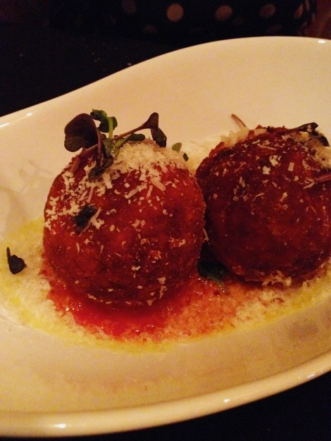 A plate of marinara sauce with prosciutto arancini.