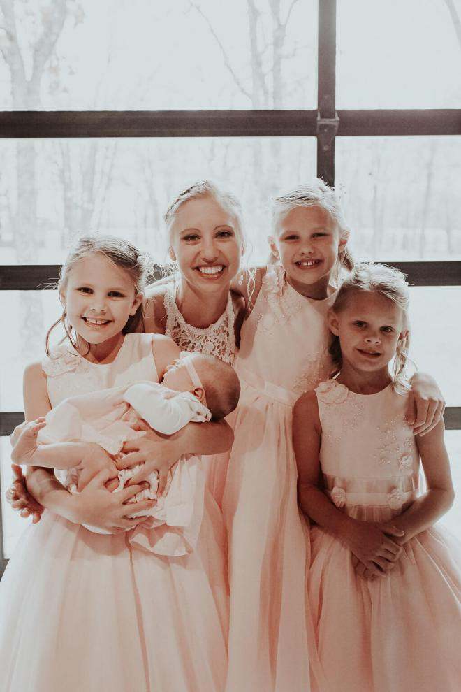The bride embraces her flower girls