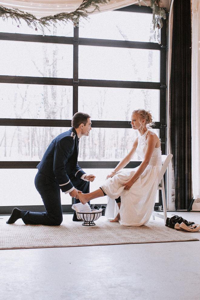 The groom kneels as he puts on the bride's garter