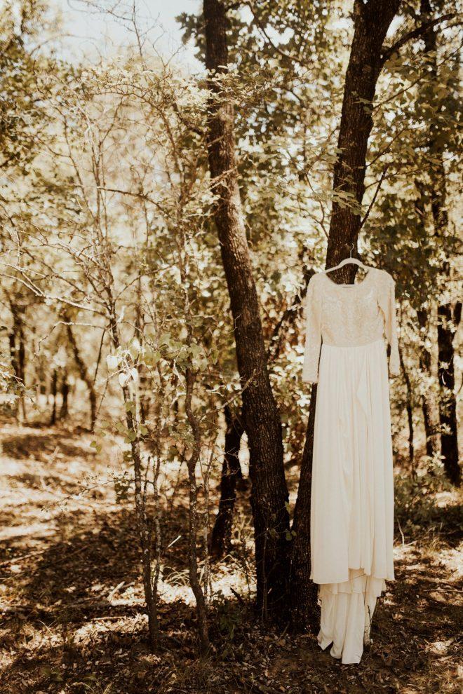 Shiloe's beautiful dress hangs from a native oak at her rustic romance wedding