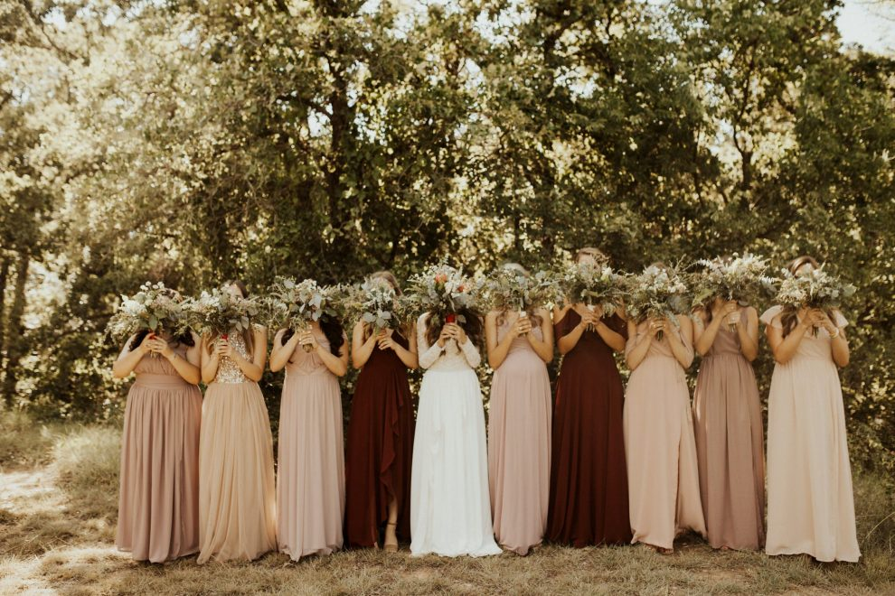 the bridesmaids and the bride hold up their wildflowers to pose for the wedding pictures