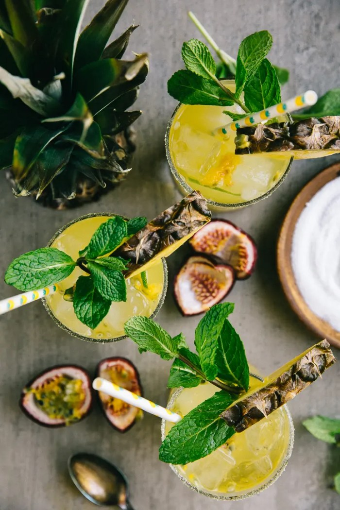 Three passion fruit pineapple margaritas on a table with straws