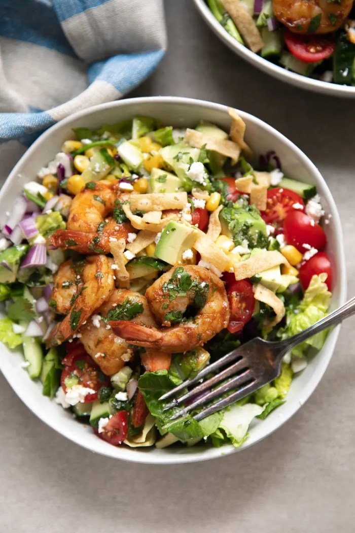 Chopped salad recipe in a white bowl with shrimp and casero cheese drizzled with cilantro lime vinaigrette