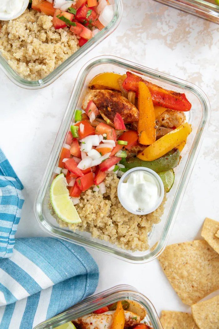 Table with glass meal prep trays filled with chicken fajitas, bell pepper, and quinoa
