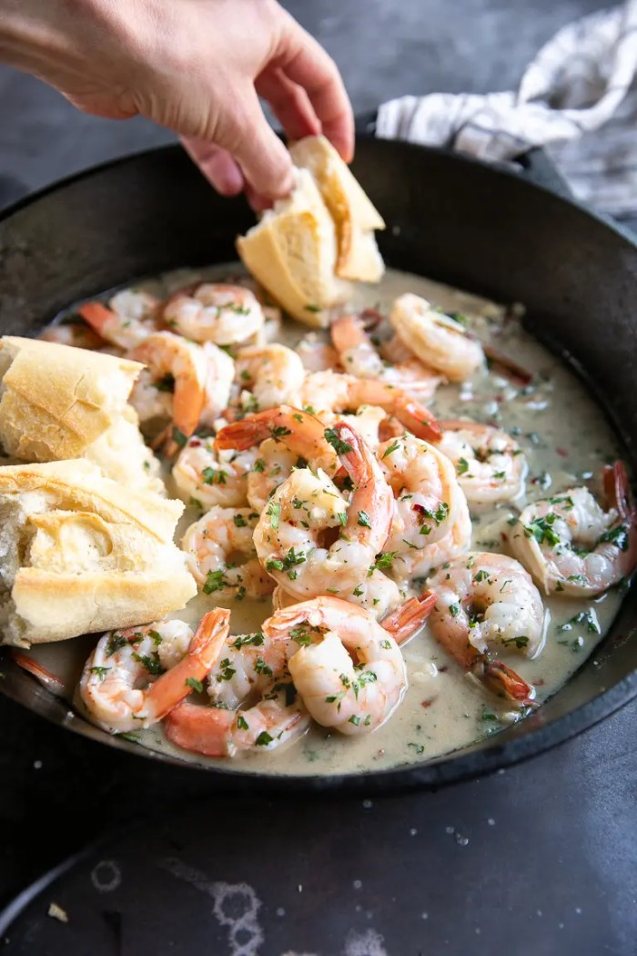 Black cast iron skillet filled with prepared shrimp scampi in a garlic butter sauce.