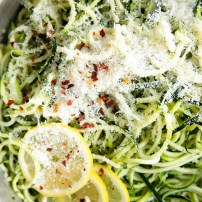 Pan filled with cooked zucchini noodles with parmesan cheese.