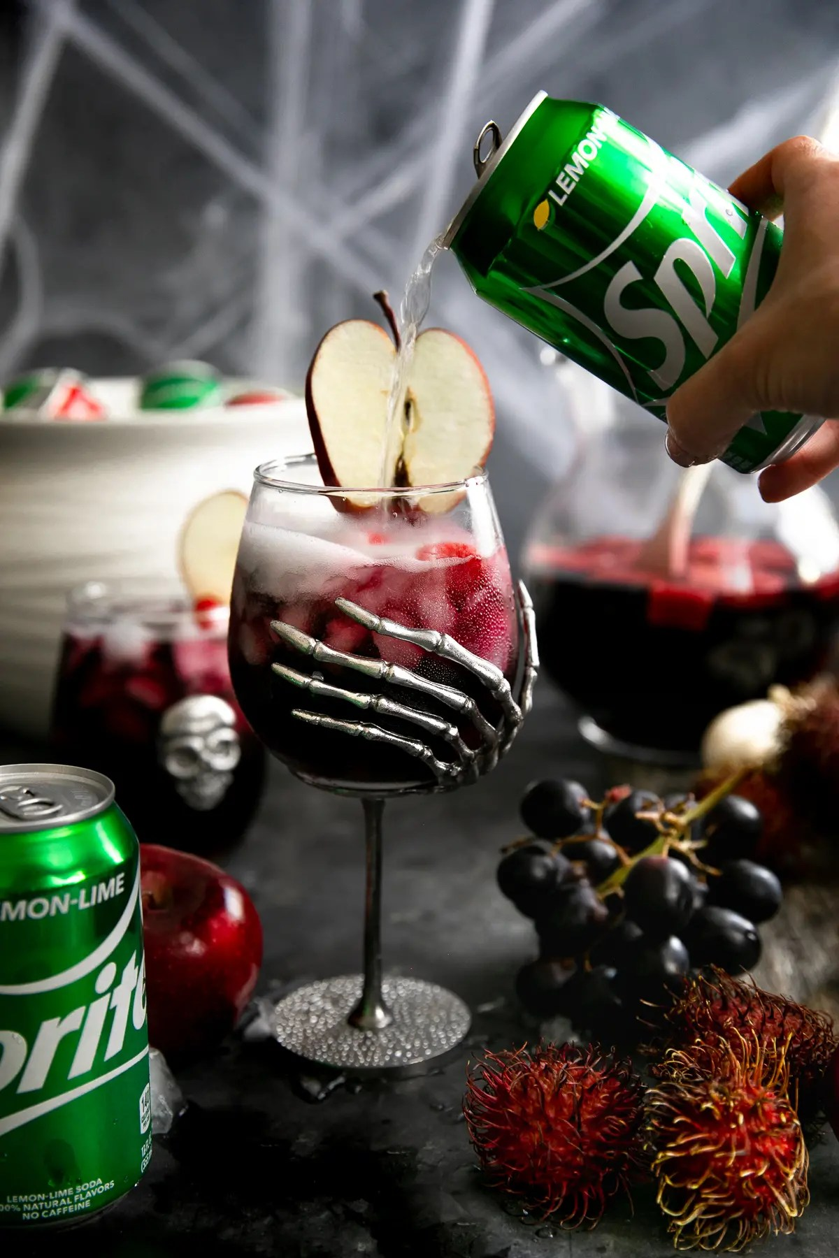 Sprite being poured into a large Halloween wine goblet filled with red sangria.
