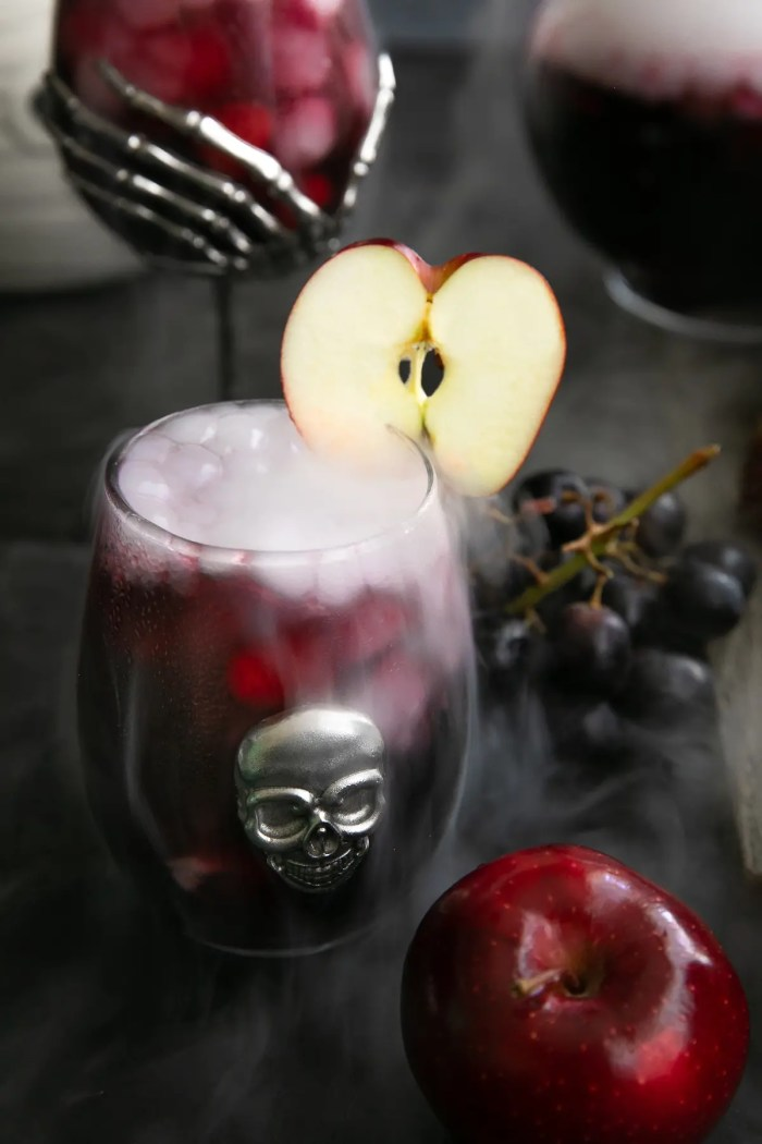 Stemless wine glass filled with red sangria and bubbling from dry ice.