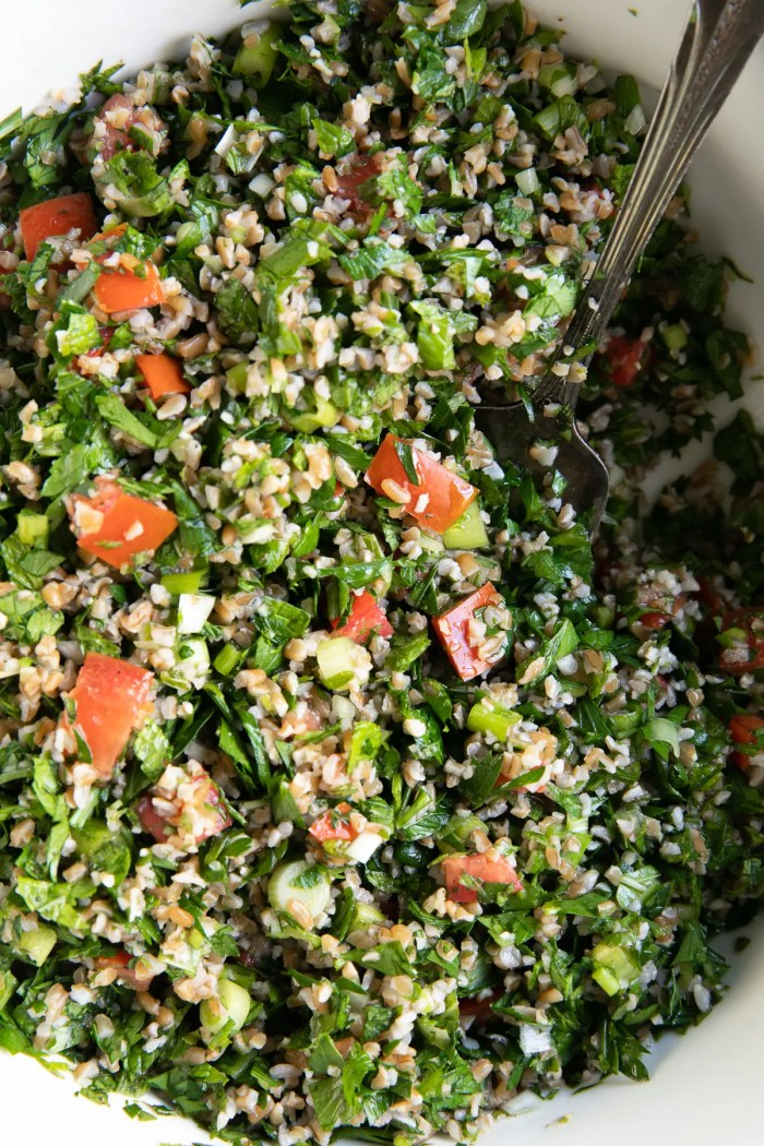 Close up overhead image of tabouli salad recipe made with fresh parsley, mint, bulgur, green onions, tomatoes, lemon juice, and olive oil.