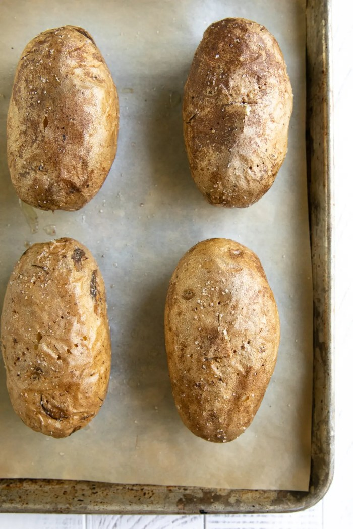 Four baked russet potatoes on a baking sheet fully cooked.