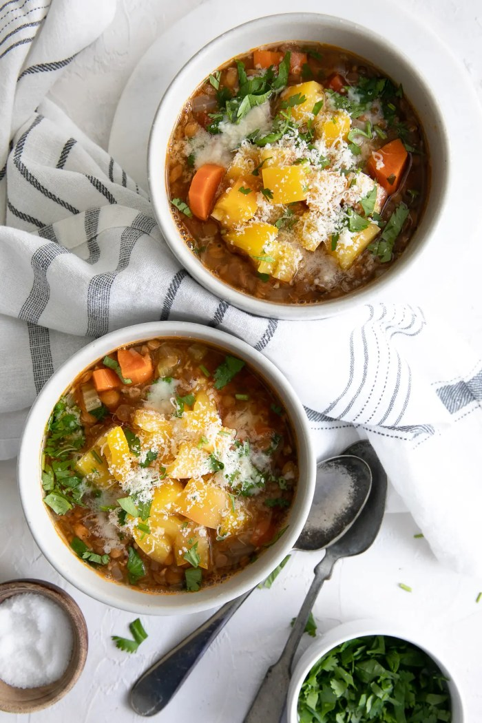 Two white bowls filled with lentil soup garnished with yellow heirloom tomatoes, chopped parsley, and grated parmesan cheese.