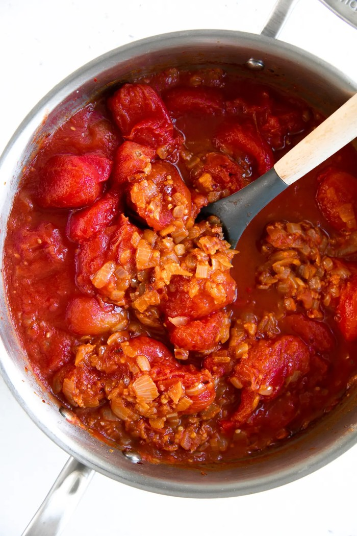 Chopped yellow onion, crushed red pepper, garlic, tomato paste, and canned whole tomatoes cooking in a large pan.