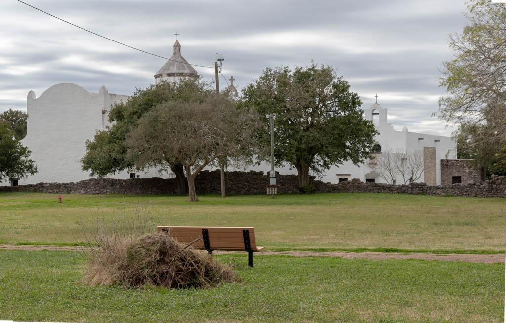 Park Bench Beside Trail With Mission Espiritu Santo Behind