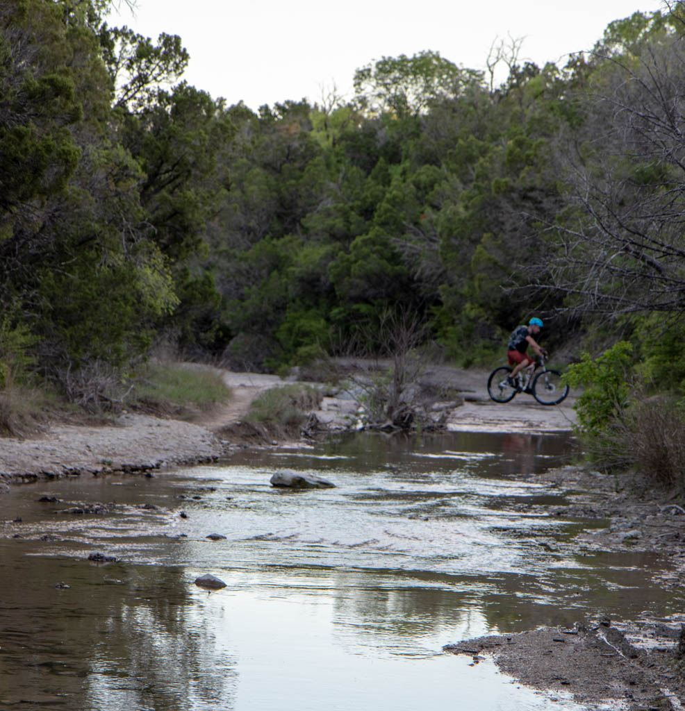 Lone Cyclist In The Stream