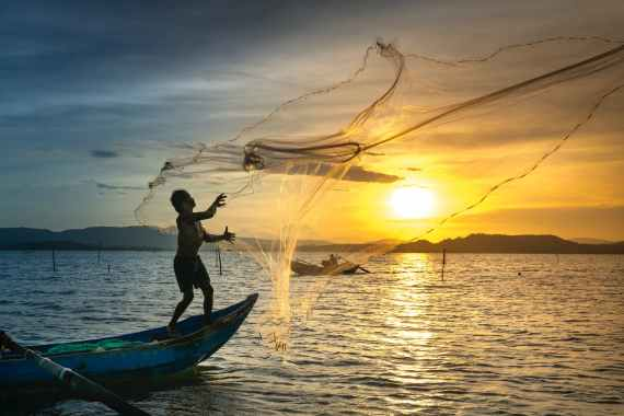 person throwing fish net while standing on boat