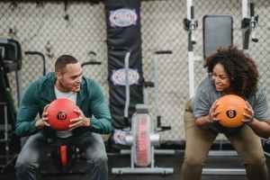 professional trainer and black woman smiling and training