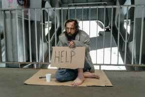 a male beggar sitting on a ground while holding a help banner