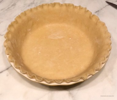 Lay the pie dough over the pie plate, trim the edges, and crimp with your fingers or a fork.
