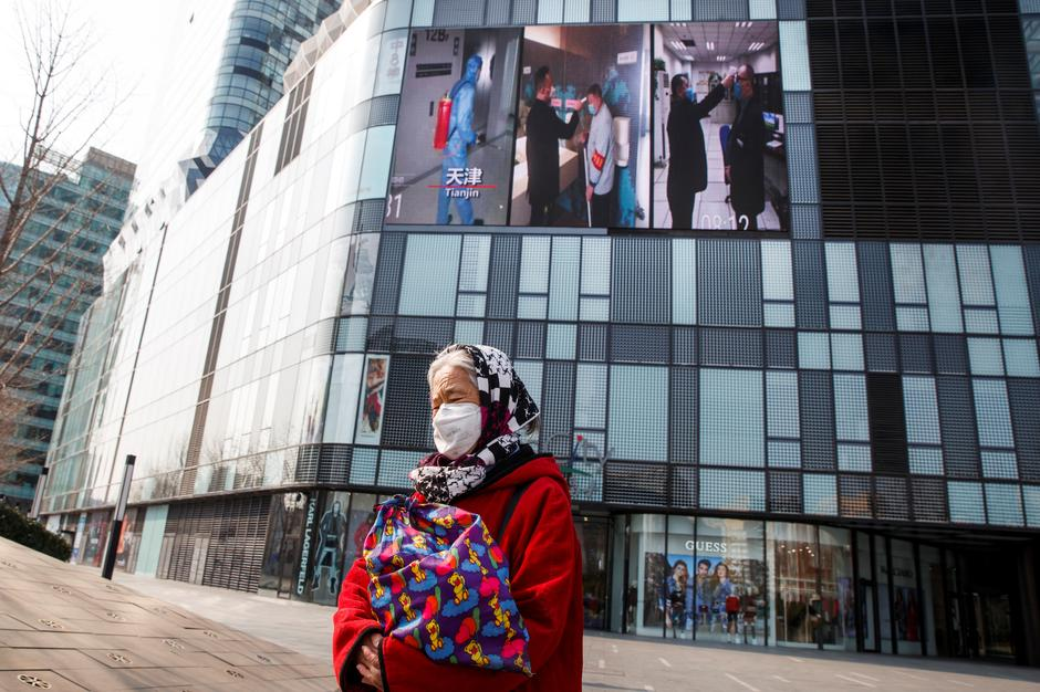 BEIJING A woman wearing a face mask walks past a screen showing a video about protective measures against the new coronavirus in China.