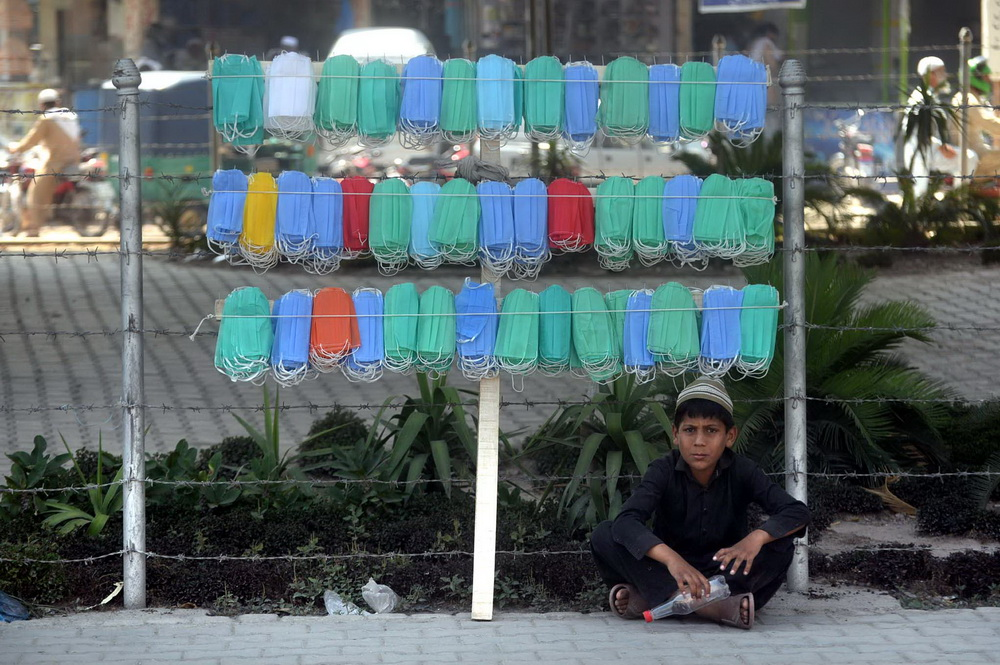 PESHAWAR A boy selling facemask at the roadside. — F.P. photo