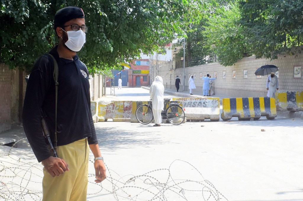 PESHAWAR A policeman standing gurad near the road leading to Gulberg No. 1 after area was sealed a part of smart lockdown with increase in coronavirus cases. — Photo by Ghulam Murtaza