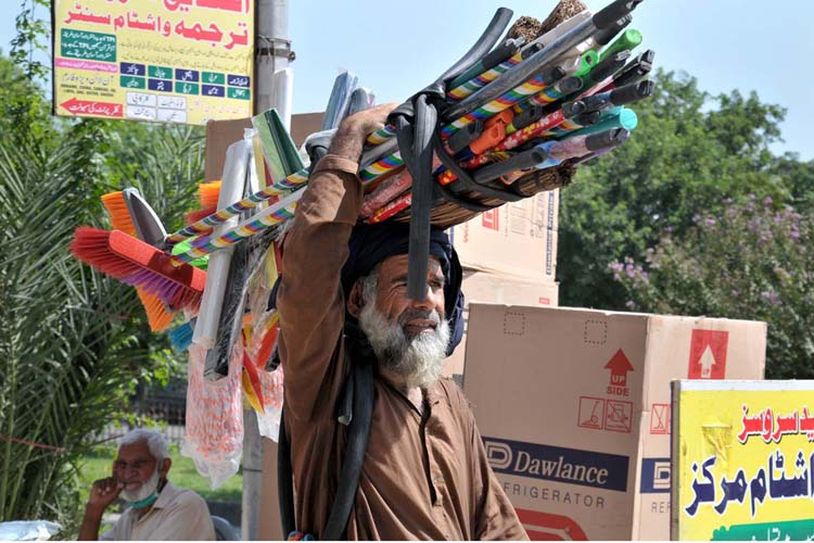 APP02-20 ISLAMABAD; September 20 – An aged person carrying domestic use items on his head and shuttles to sell for livelihood at Aabpara market. APP photo by Saeed-ul-Mulk