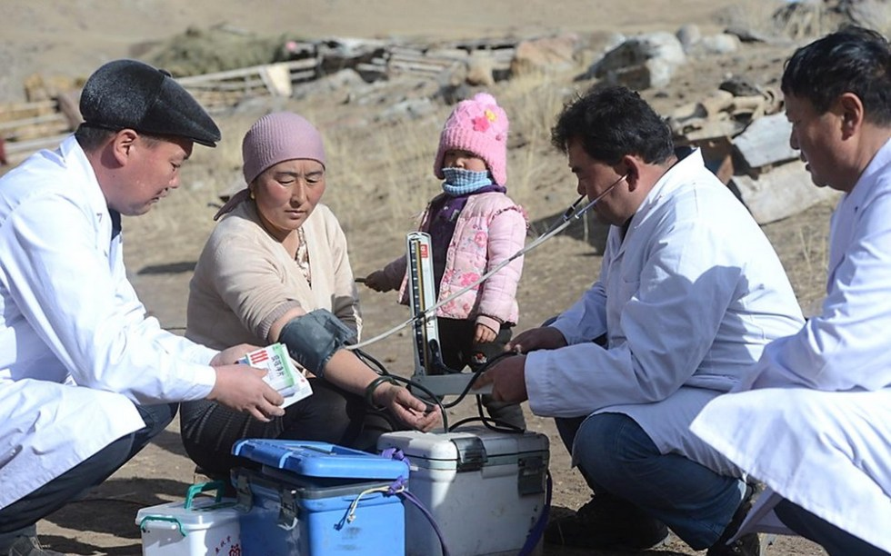 Xinjiang, CHINA Healthworkers checking the blood pressure of a woman shepherd.