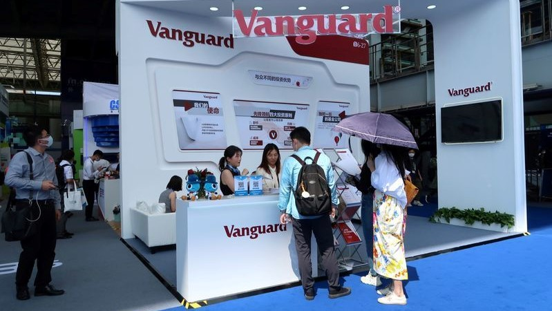 FILE PHOTO: People are seen at a booth of Vanguard Group at a fair during the INCLUSION fintech conference in Shanghai, China September 24, 2020. REUTERS/Cheng Leng
